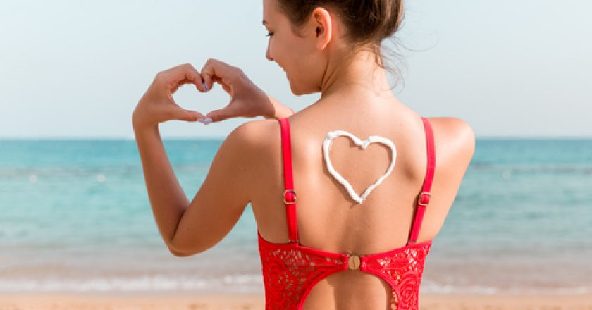 Beautiful girl in red swimsuit with sunscreen in shape of heart at the back at the beach | © Mykola Sosiukin | Dreamstime Stock Photos