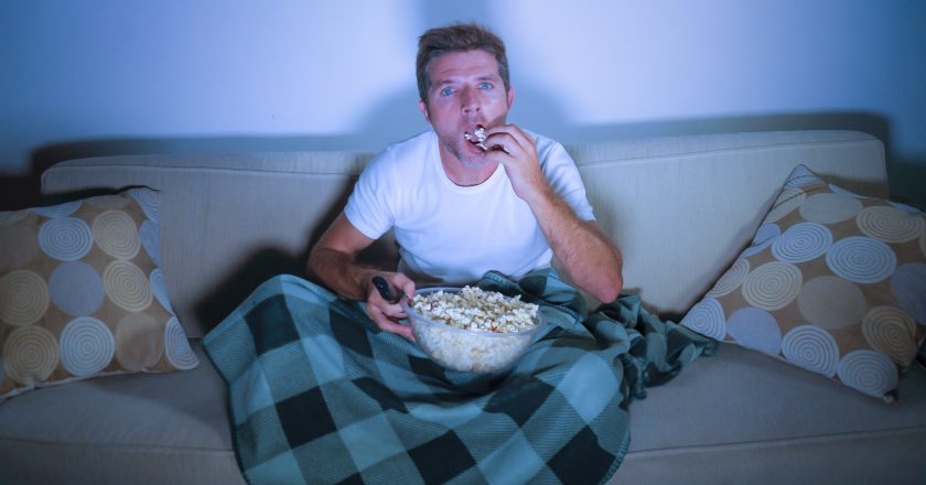 Lifestyle portrait of young attractive relaxed man watching movie on television eating popcorn sitting late night at living room s