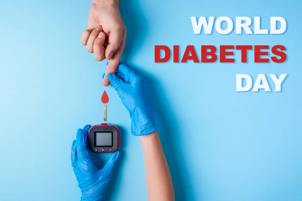 Inscription world diabetes day, Nurse making a blood test. Man`s hand with red blood drop and Glucose meter