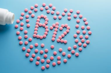Pink tablets in the form of B12 in the heart on a blue background, spilled from a white can
