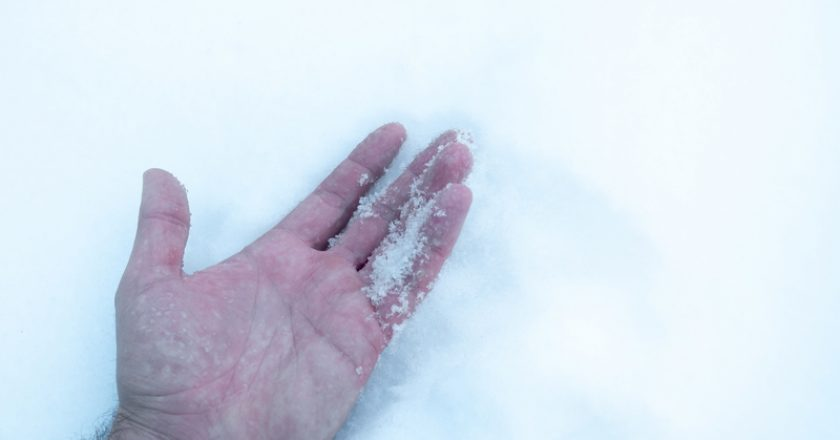 The man`s hand in the snow, frozen got hypothermia frostbite