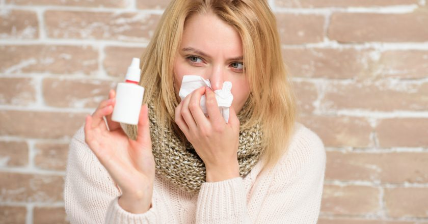 Feeling stuffy. Sick woman injecting drops into nose. Pretty girl with runny nose holding nasal drops. Cute woman