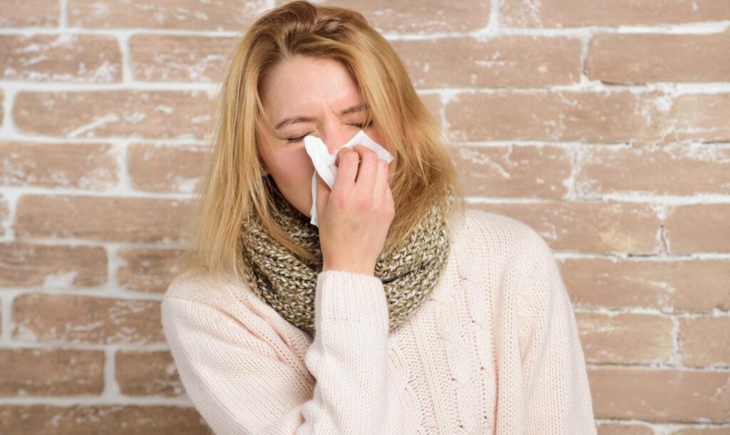 Sneezing non stop. Pretty girl sneezing of seasonal influenza virus. Cute woman caught nasal cold or allergic rhinitis