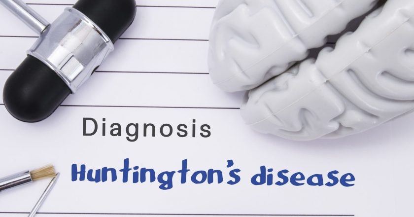 Neurological diagnosis of Huntington`s disease. Neurological hammer, human brain figure, tools for sensitivity testing are on tabl