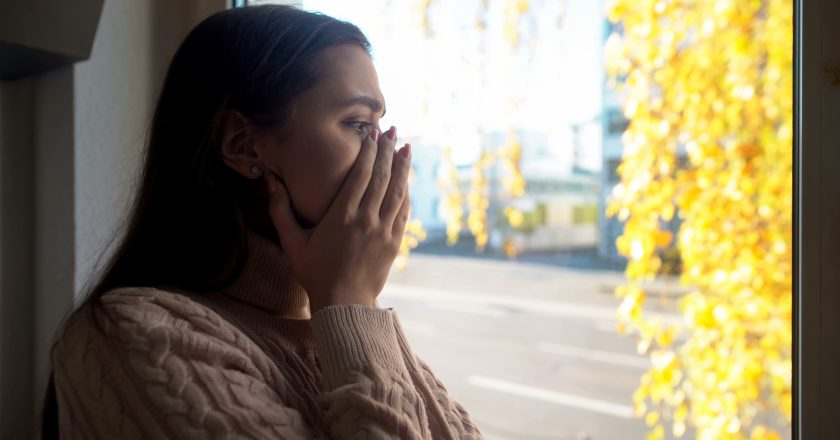 Crying lady looking through window, afraid of going outdoors agoraphobia disease