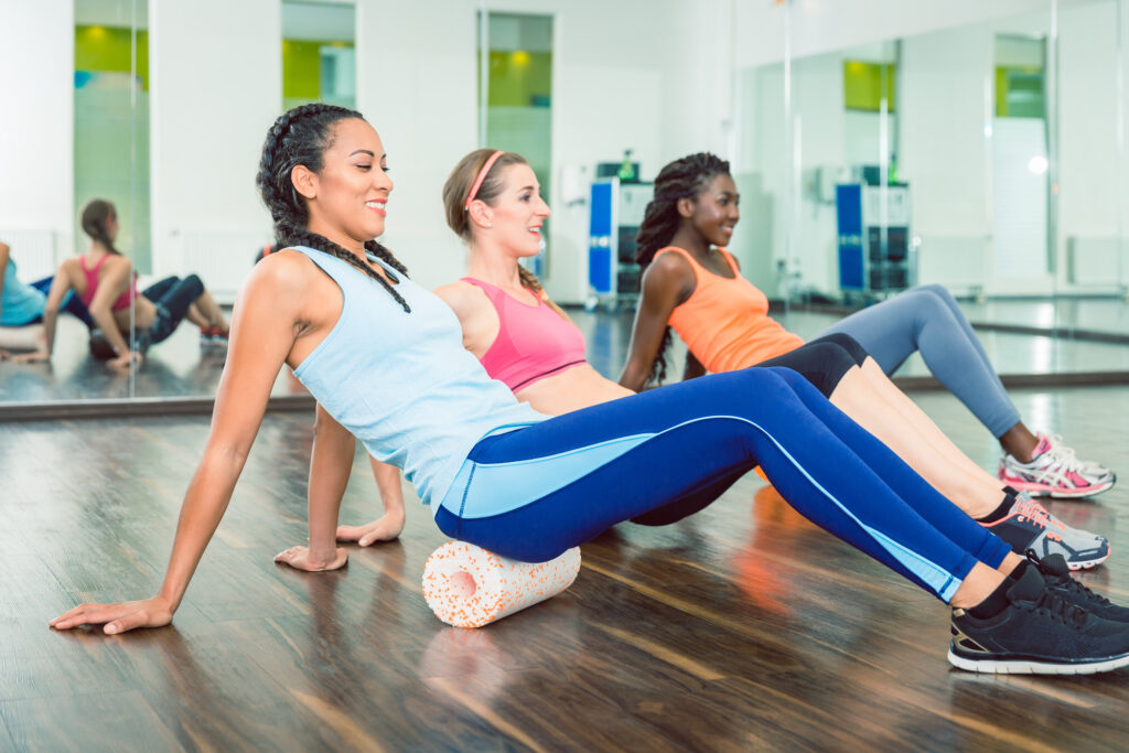 Fit beautiful woman exercising on foam roller during group workout class | © Arne9001 | Dreamstime Stock Photos
