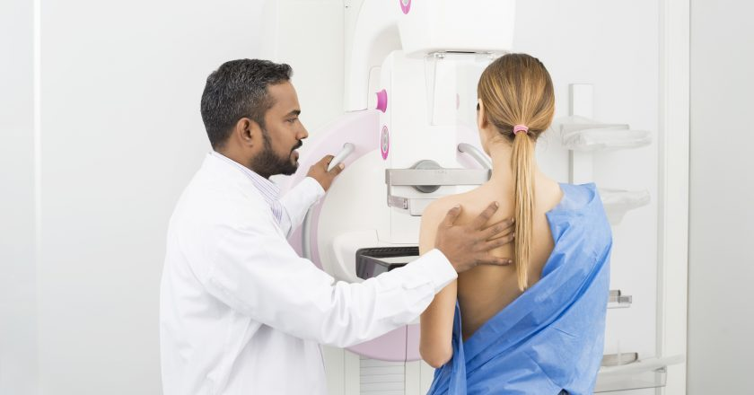 Doctor Standing Assisting Patient Undergoing Mammogram X-ray Tes | © Tyler Olson | Dreamstime Stock Photos
