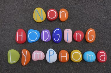 Non-Hodgkin Lymphoma text composed with multi colored stones over black volcanic sand