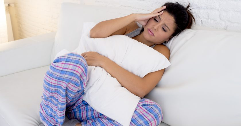 Beautiful hispanic woman in painful expression holding belly suffering menstrual period pain