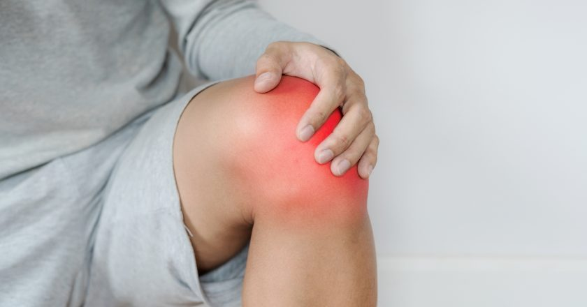 A man touching knee with red highlights concept of knee and joint pain |
