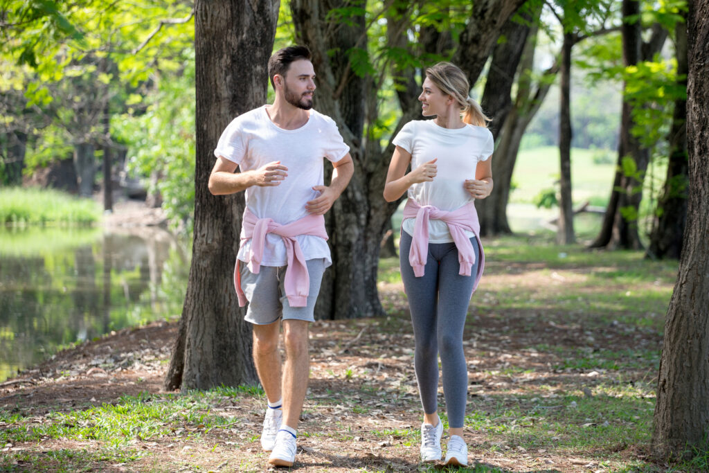 young couple fitness in sportswear running together in park . sport man and woman jogging outdoors in nature. workout ,exercising |