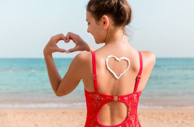 Beautiful girl in red swimsuit with sunscreen in shape of heart at the back at the beach   © Mykola Sosiukin   Dreamstime Stock Photos