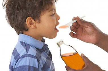 Sick child taking syrup against cough or flu |