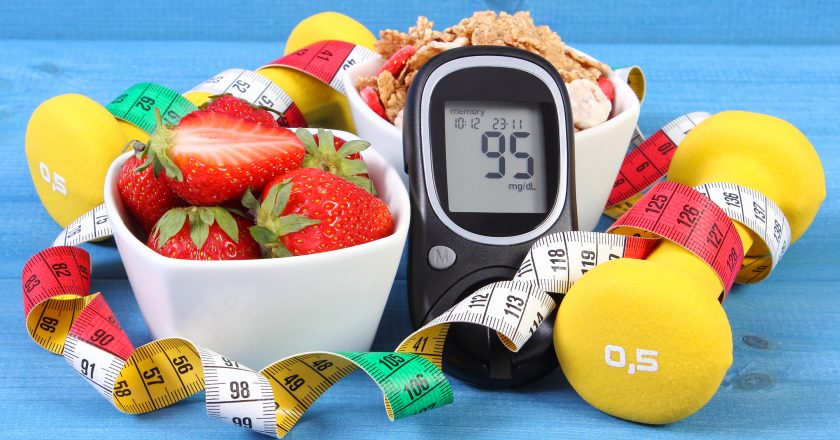 Glucometer with sugar level, healthy food, dumbbells and centimeter, diabetes, healthy and sporty lifestyle |