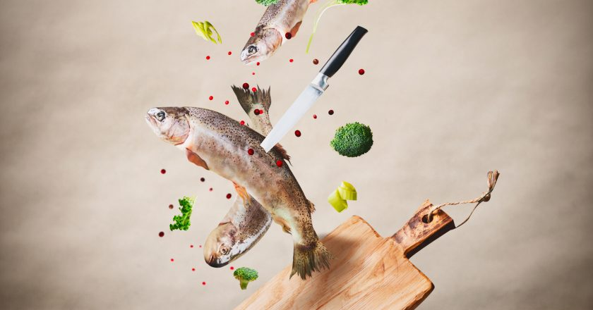 Flying raw whole trout fishes with vegetables, oil and spices ingredients above wooden cutting board for tasty cooking on desk kit |  |