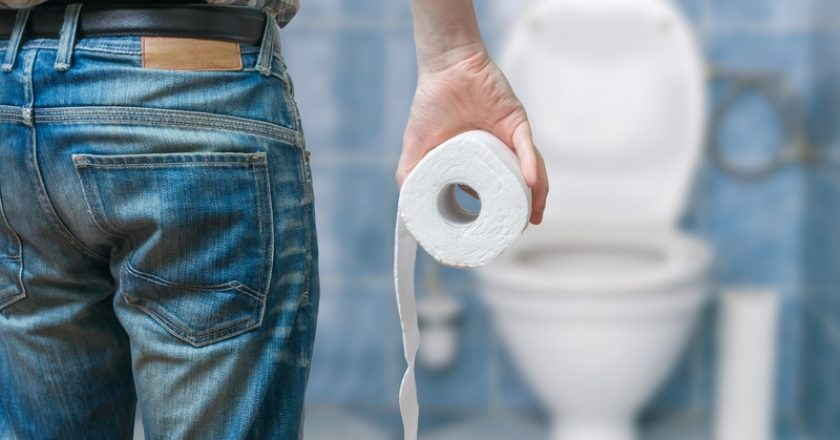 Man suffers from diarrhea holds toilet paper roll in front of toilet bowl
