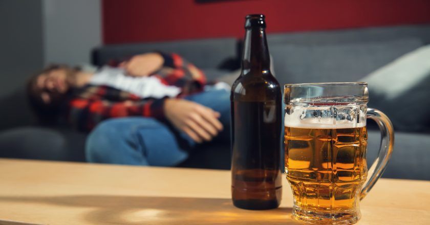 Bottle and mug of beer on table and blurred drunk man sleeping on sofa at home. Alcoholism concept