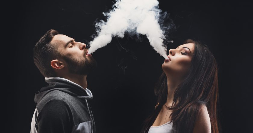 Young couple vaping e-cigarette with smoke on black closeup |
