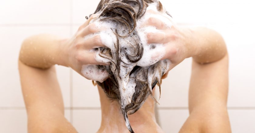 Woman washing her hair in shower |