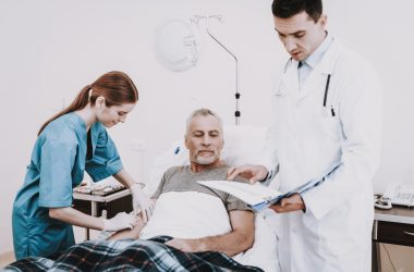 People in Hospital. Doctor and Nurse Help Old Man |