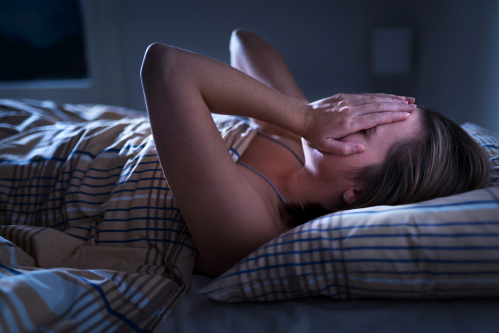 Insomnia, sleep apnea or stress concept. Sleepless woman awake and covering face in the middle of the night. |