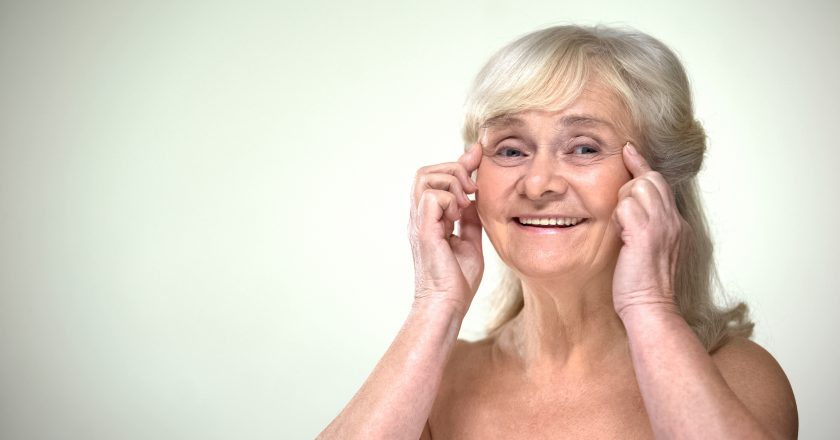 Attractive old lady doing facial exercises, anti-aging facebuilding for eyes |
