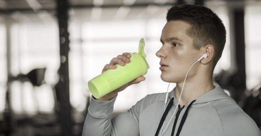Young guy drinks sports nutrition in gym  