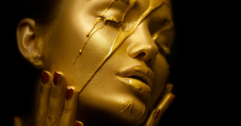 Sexy beauty woman with golden metallic skin. Gold paint smudges drips from the face and sexy lips
