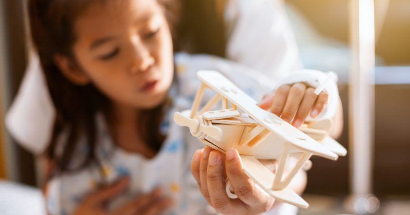 Sick asian child girl playing with toy wooden airplane with her mother while stay in the hospital |