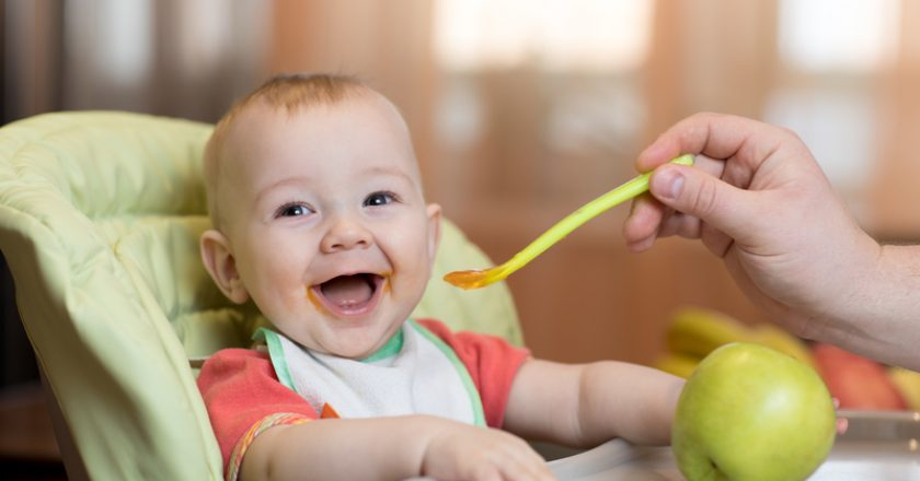 Baby eating healthy food with father help at home | © Oksun70 | Dreamstime Stock Photos