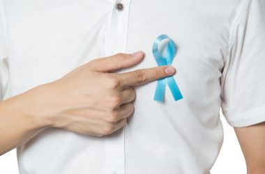 Men`s healthcare concept - close up of male hand pointing to light blue ribbon for prostate cancer at left chest isolated | © Thatpichai | Dreamstime Stock Photos