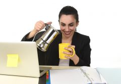 Business woman at laptop computer desk drinking coffee excited and anxious in caffeine addiction | © Ocusfocus | Dreamstime Stock Photos