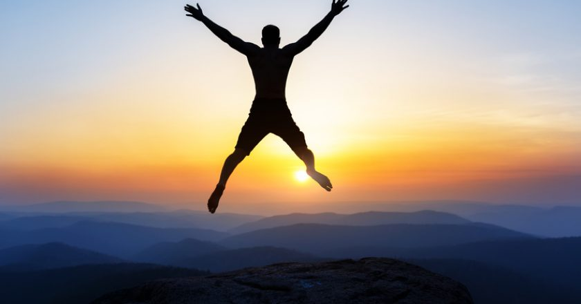 Happy man jumping for joy on the peak of the mountain, cliff at sunset. Success, winner, happiness | © Igor Meynson | Dreamstime Stock Photos