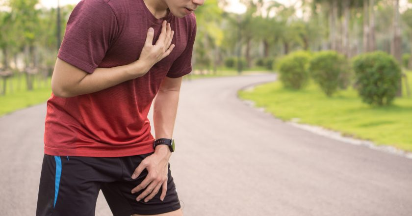 Sport man having heart attack or chest pain after running workout at park. Sport and Health care concept