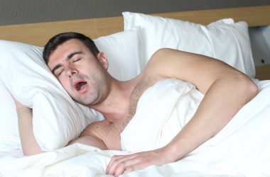 Male in bed with sleep apnea disorder |