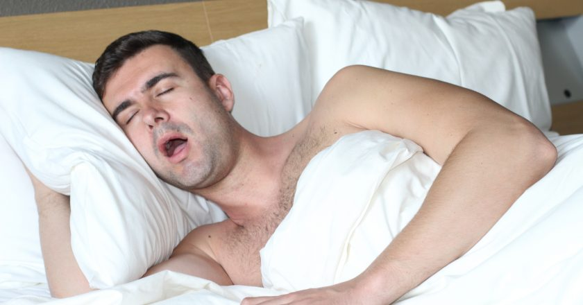 Male in bed with sleep apnea disorder |