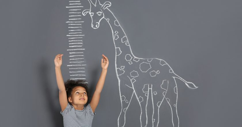 African-American child measuring height near chalk giraffe drawing on grey |