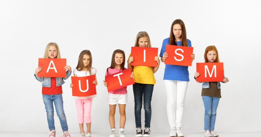 Autism. Group of children with red banners isolated in white | © Volodymyr Melnyk | Dreamstime Stock Photos