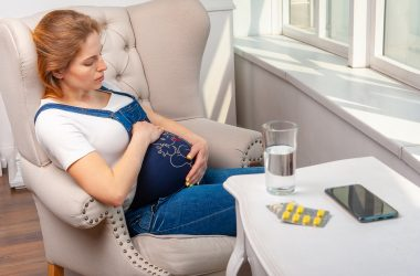 Illness during pregnancy. Woman sitting at home and taking medical drugs |