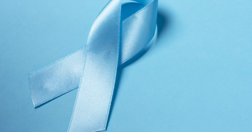 Closeup a Blue satin Ribbon symbol of prostate cancer awareness on a bright blue background. |