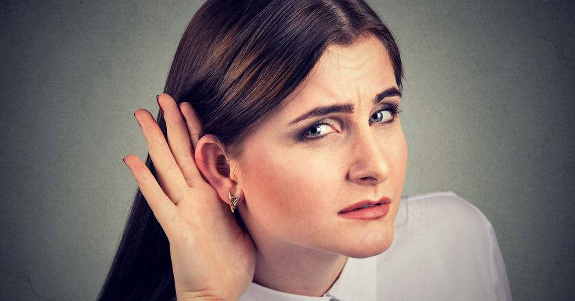 Woman with a hearing loss cupping her hand behind ear to try and amplify available sound |  |