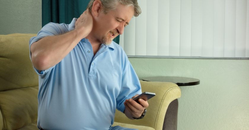 Man with bad case of Tablet Neck Syndrome a chronic pain condition from Tech Addiction using smartphone too much | © Mike2focus | Dreamstime Stock Photos