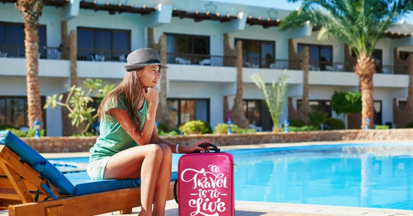 Travel, summer holidays and vacation concept - Beautiful woman walking near hotel pool area with red suitcase in Egypt   © Timonko   Dreamstime Stock Photos