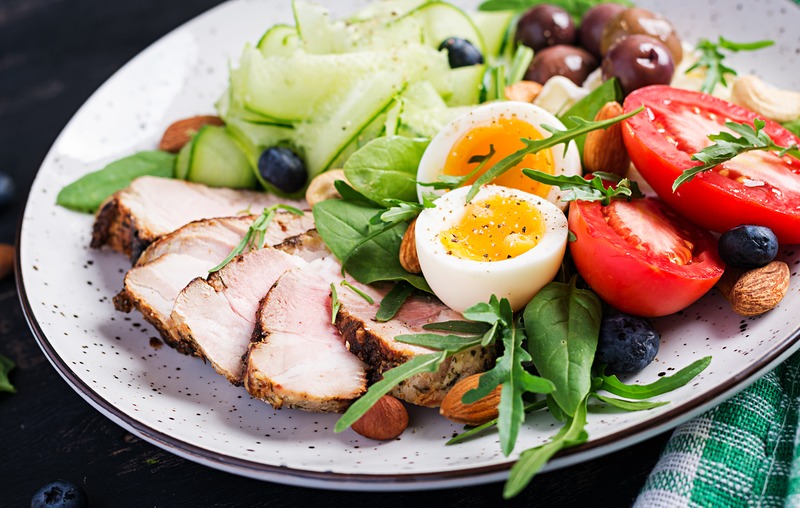 Ketogenic diet. Boiled egg, pork steak and olives, cucumber, spinach, brie cheese, nuts and tomato | © Timolina | Dreamstime Stock Photos