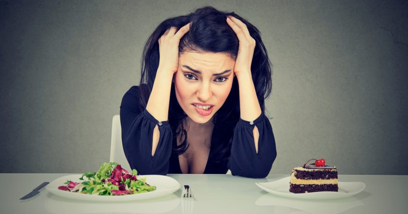 Woman tired of diet restrictions deciding to eat healthy food or cake she is craving | © Kiosea39 | Dreamstime Stock Photos