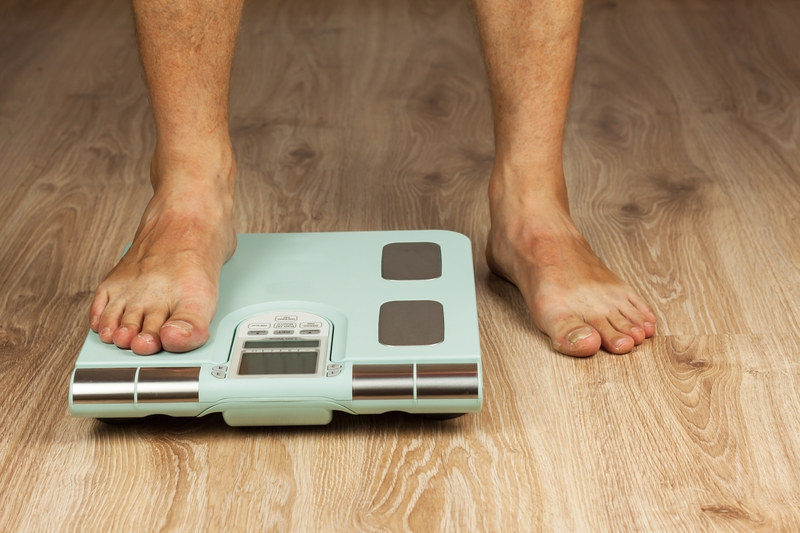 The old man is standing on a modern scale. Measuring the fat content of the body. Intelligent medical weight. The concept of obesi | © Martin Šandera | Dreamstime Stock Photos