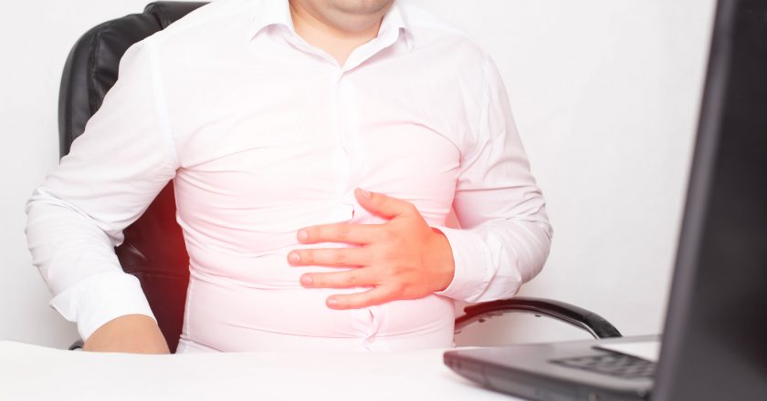 Male office worker holding stomach stomach, gastritis and stomach ulcer, Helicobacter pylori