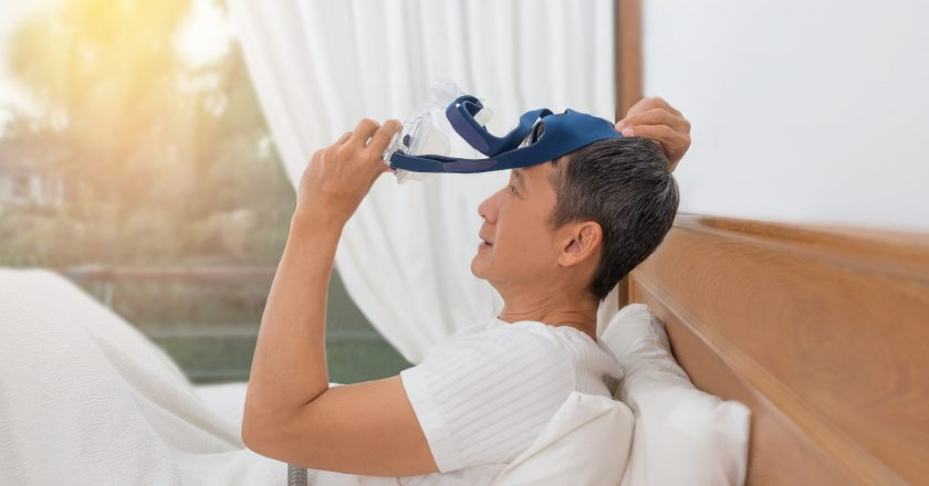 Man lay in bed wearing CPAP mask ,sleep apnea therapy.