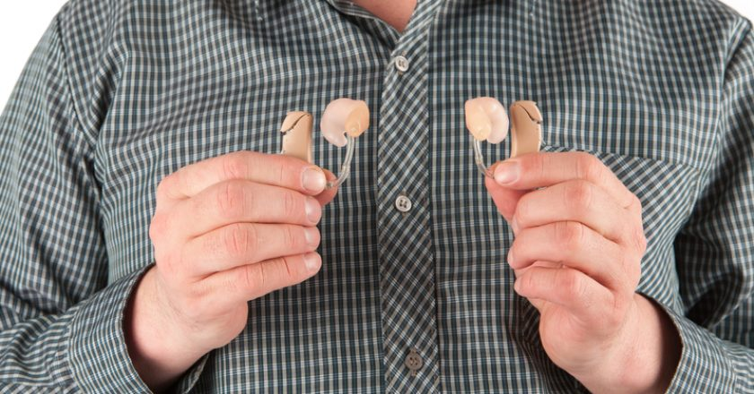 Man holding two hearing aids