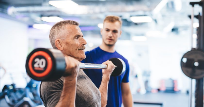 Older man lifting weights, supervised by gym assistant. | © Niserin | Dreamstime Stock Photos